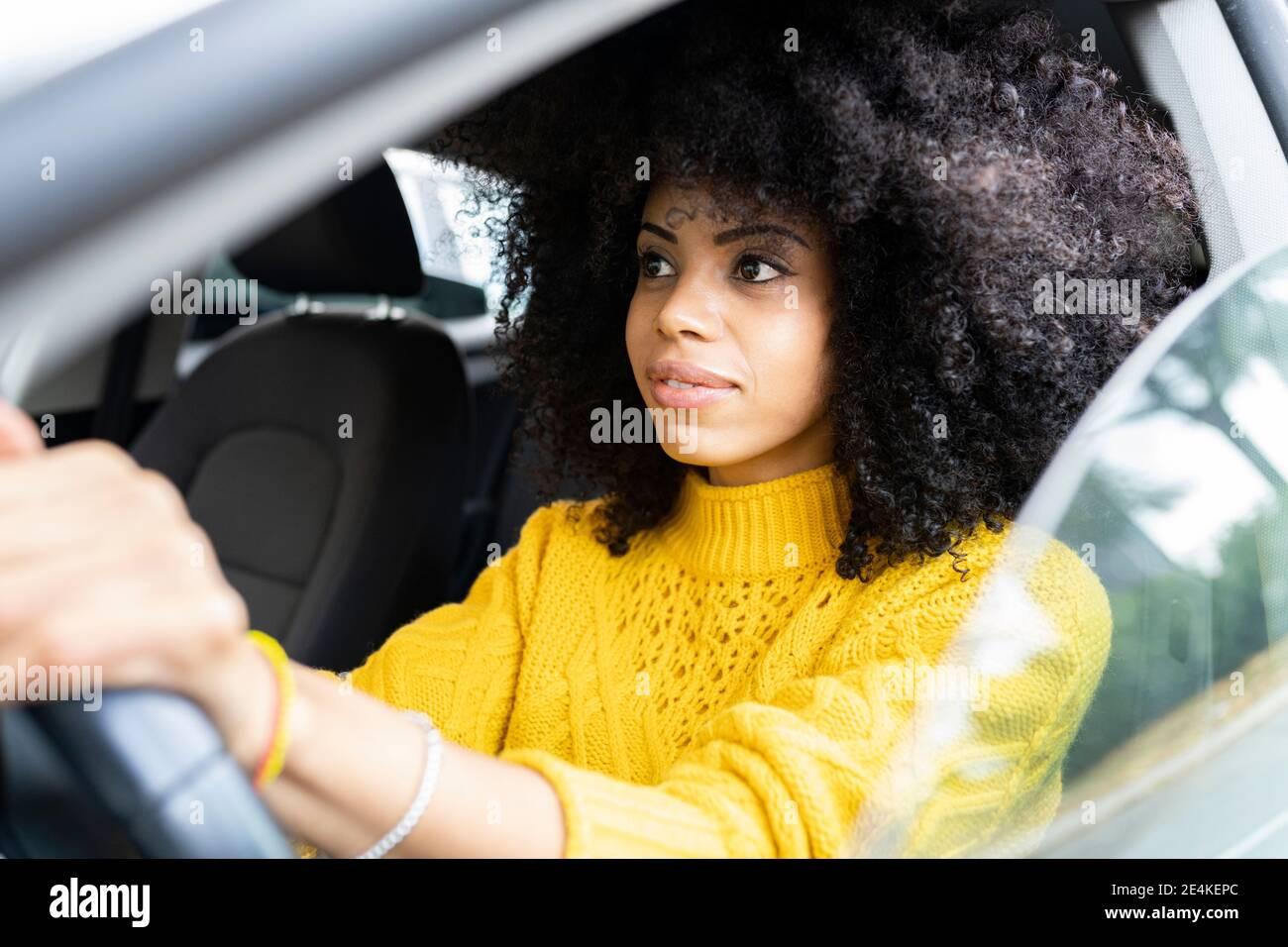 Mujer joven concentrándose mientras conduce el coche Foto de stock