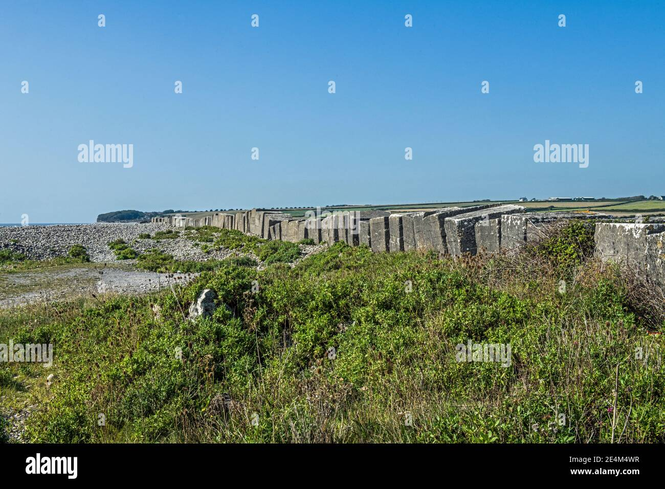 La playa de Aberthaw muestra guijarros y bloques antitanque en la Costa del Patrimonio de Glamourgan, Vale de Glamourgan Gales del Sur Foto de stock