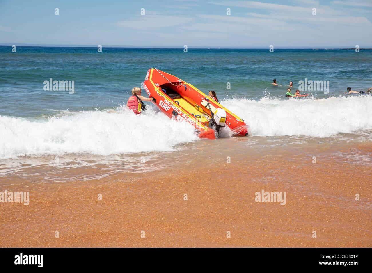 Los salvavidas de rescate de surf voluntarios lanzan rescate de surf zodiaco rojo inflable Barco en la playa de Bilgola en Sydney, Nueva Gales del Sur, Australia Foto de stock
