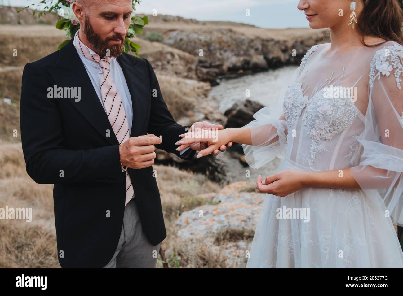 Un hombre le propone a una mujer que se involucre poniendo un anillo en su dedo. Foto de stock