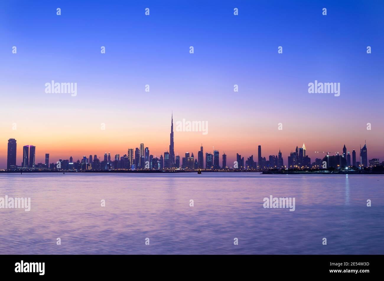Vista panorámica del horizonte de Dubai con Burj khalifa y. otros rascacielos capturados en la puesta de sol con la hermosa Cielo azul en el dubai creek Foto de stock