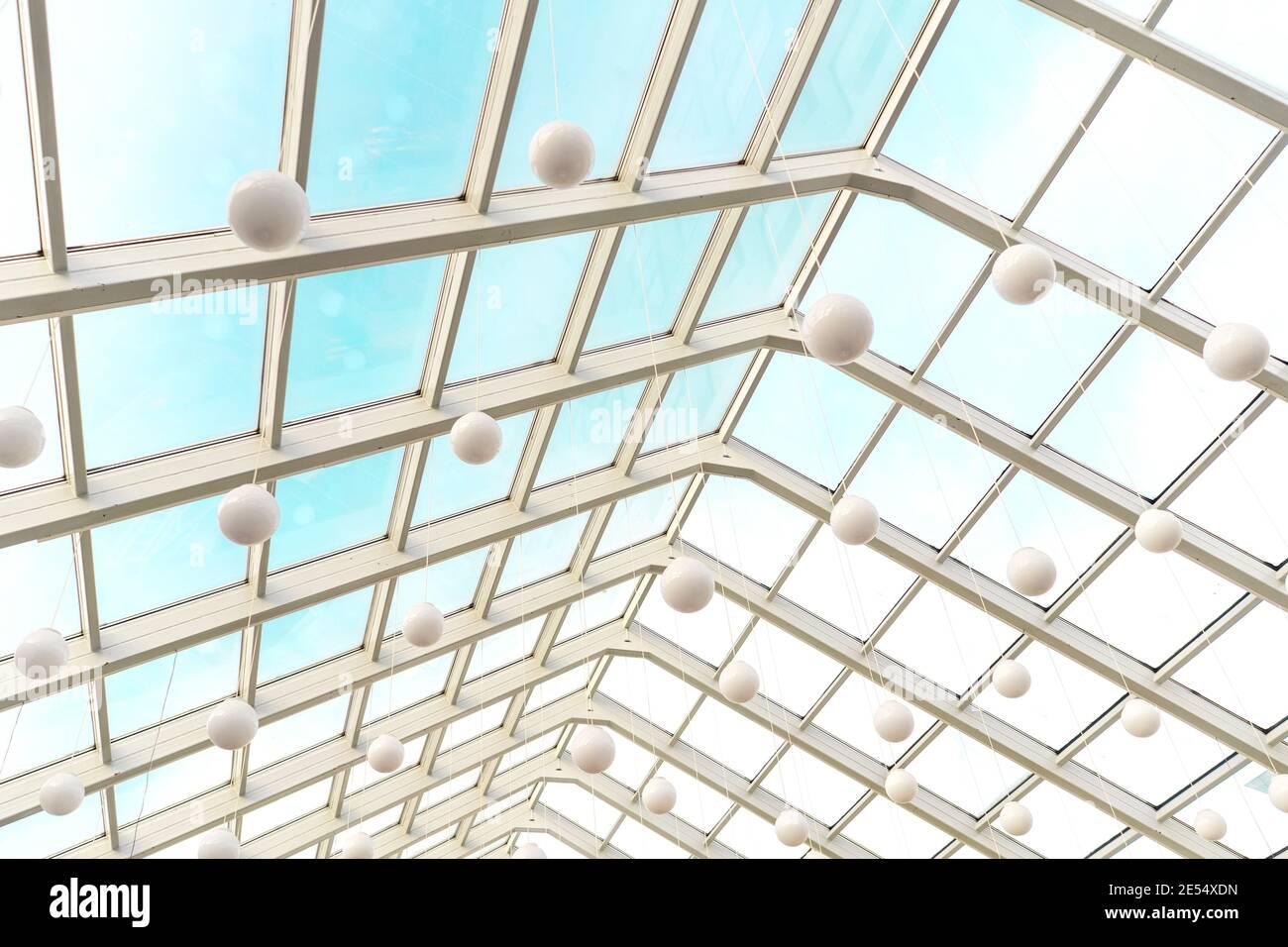 Techo moderno y transparente en interior futurista con arcos blancos en perspectiva. Lámparas esférico blancas. Foto de stock