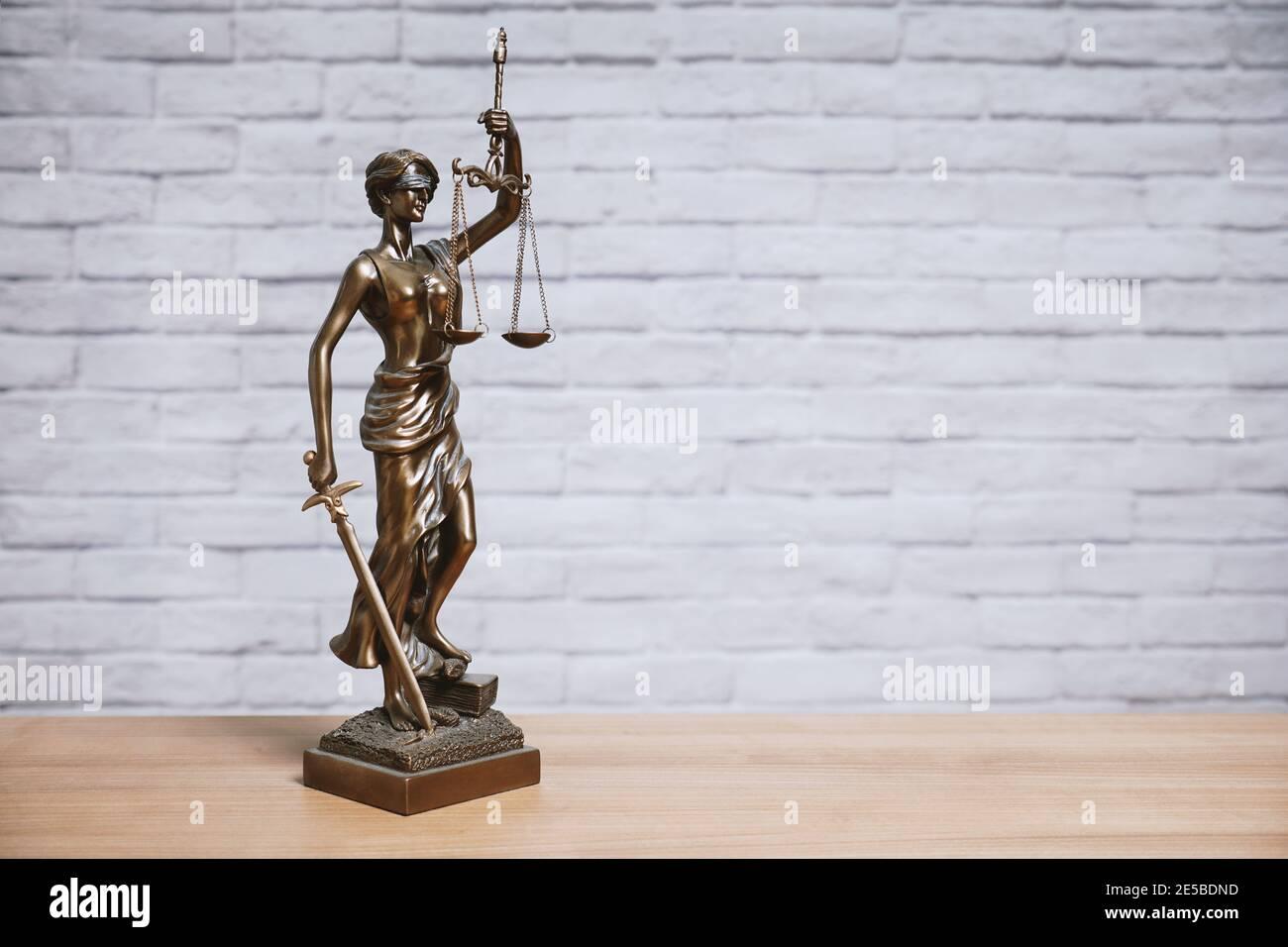 Lady Justice o Justitia la diosa de la justicia sobre la estatua escritorio - derecho legal legislación concepto - ladrillo pared fondo con espacio de copia Foto de stock