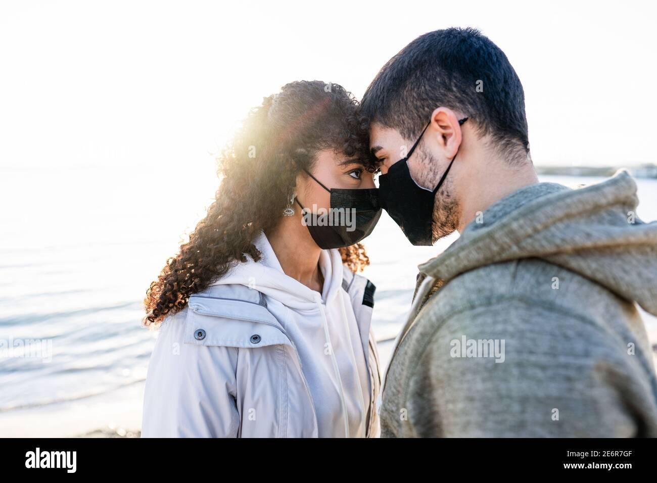 Nueva pareja normal en problemas de amor debido a distanciamiento social: Hombre y novia mirando en los ojos uno a otro cabeza con el sol de puesta refl Foto de stock