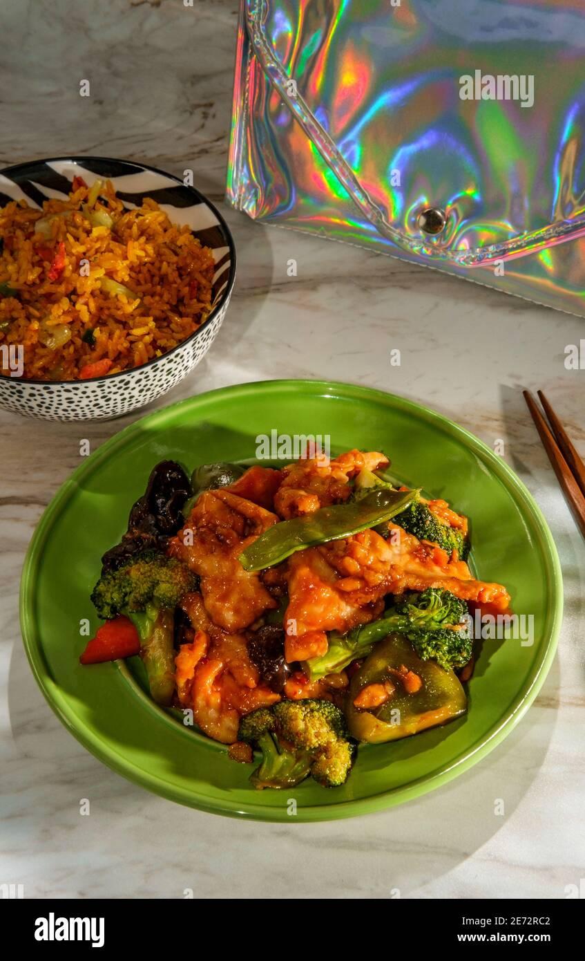 Pollo de ajo chino con verduras mixtas salteadas y lado de arroz frito de cerdo Foto de stock