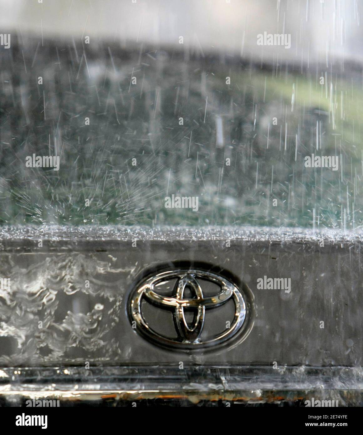 Toyota Motor Corp's logo on a car is seen during a demonstration of the hi-function shower test at its quality control facility in the headquarters in Toyota, central Japan, March 30, 2010.    REUTERS/Kim Kyung-Hoon (JAPAN - Tags: TRANSPORT BUSINESS) Foto de stock