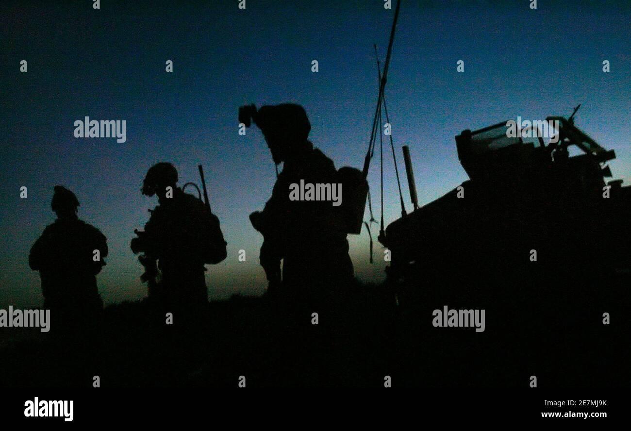 Los soldados del ejército estadounidense se encuentran cerca de su vehículo antes del amanecer mientras se preparan para participar en una operación conjunta con soldados iraquíes cerca de Mahmudiya, al sur de Bagdad 16 de abril de 2007. REUTERS/Bob Strong (IRAK) Foto de stock