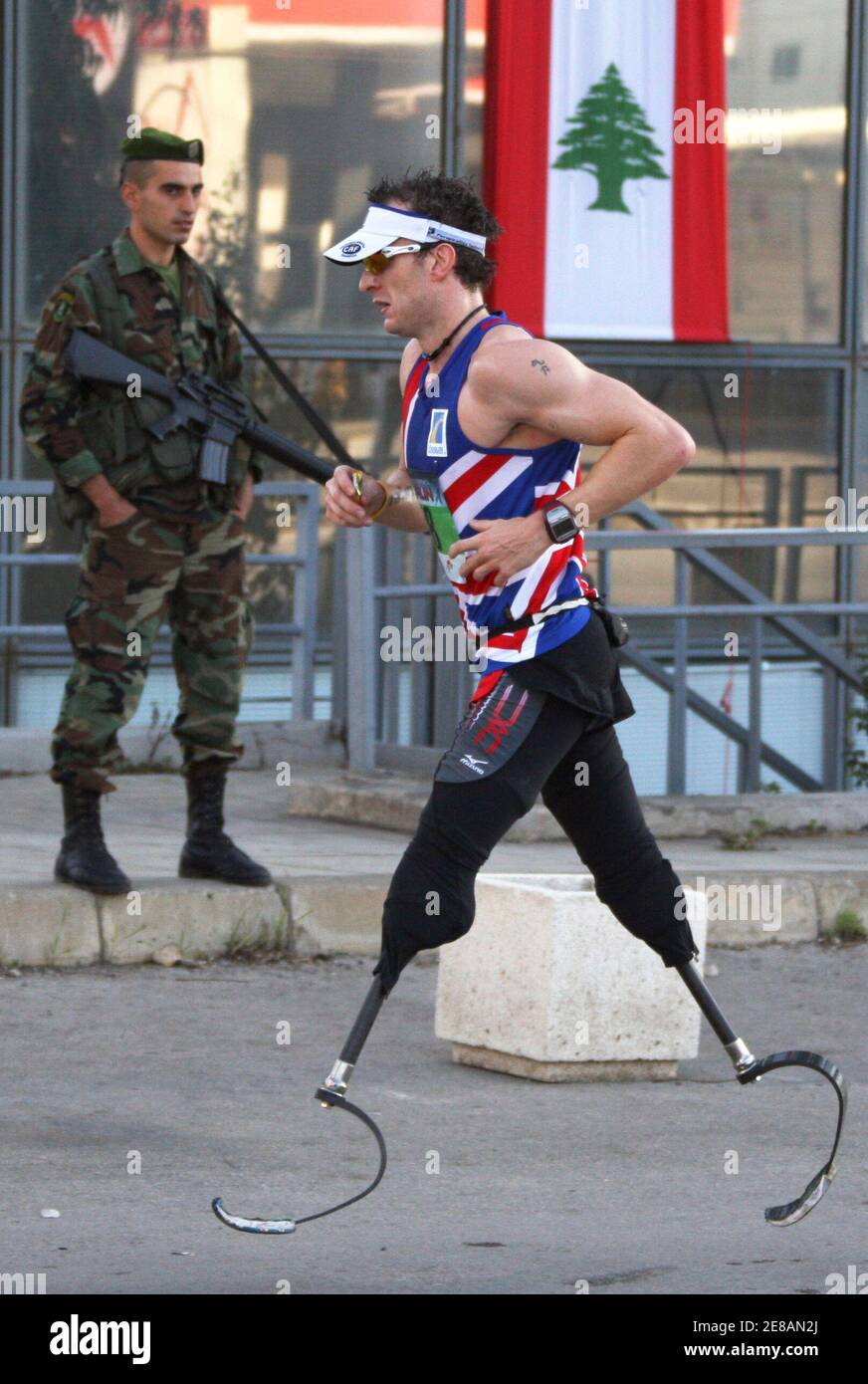 Richard Whitehead, a British disability activist who was born without legs, competes as he runs past a Lebanese soldier during the annual Beirut Marathon in Beirut, November 30, 2008. Thousands of people took part in the run which started in the Lebanese capital.     REUTERS/ Mohamed Azakir  (LEBANON) Foto de stock