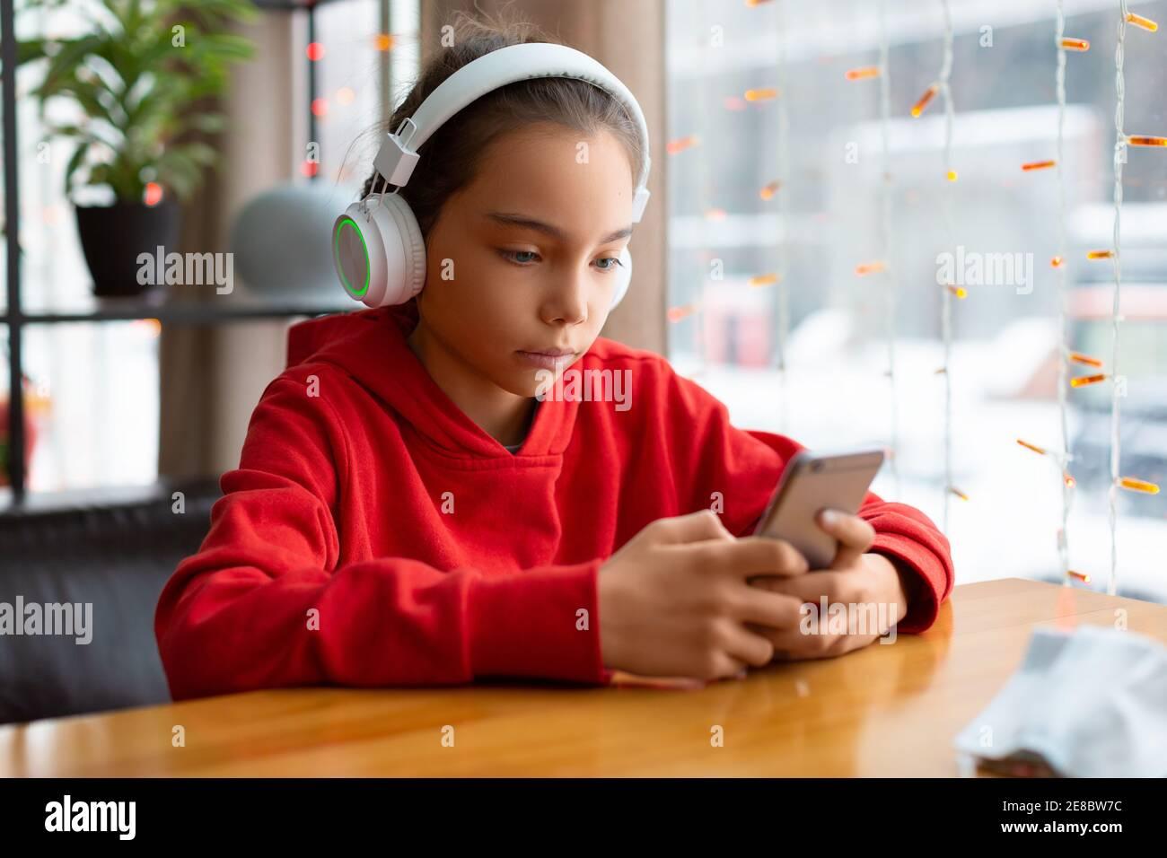 Foto de una adolescente en unos auriculares blancos durante las conversaciones en línea con amigos. Concepto de tecnología moderna. Foto de stock
