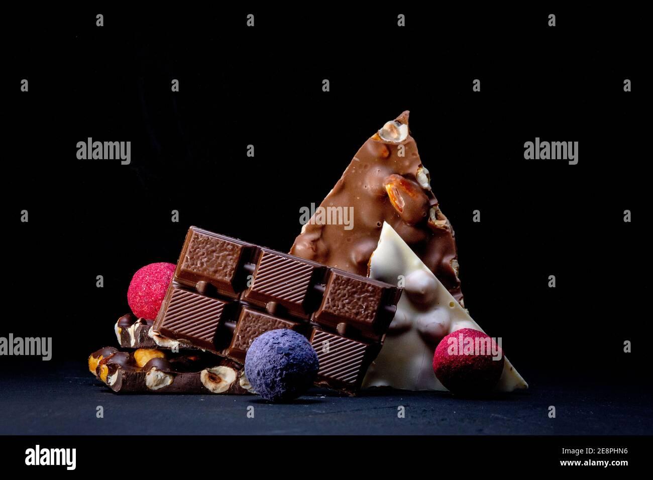 Trufa de chocolate con trozos de chocolate y polvo de cacao volador sobre un fondo oscuro. Foto de stock