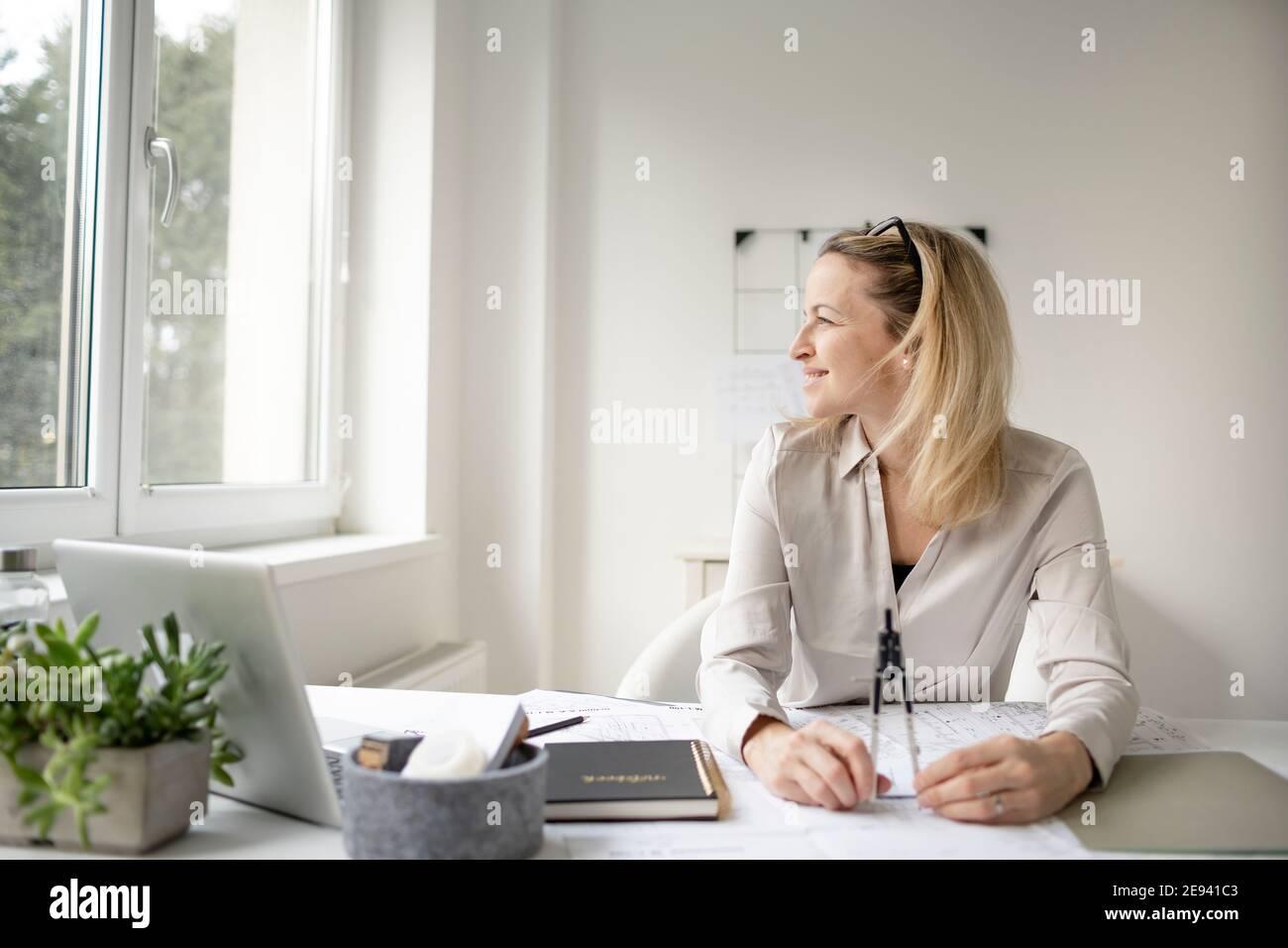 rubia, hermosa mujer arquitecto está sentado en su oficina y está soñando con mejores tiempos sin corona Foto de stock