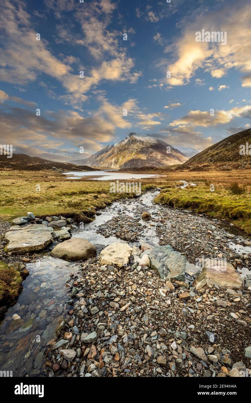 Paso de piedras a través de un arroyo que conduce al lago Idwal en la Reserva Natural de Cwm Idwal con la montaña Pen yr Ole Wen en el fondo, Snowdonia, Gales Foto de stock