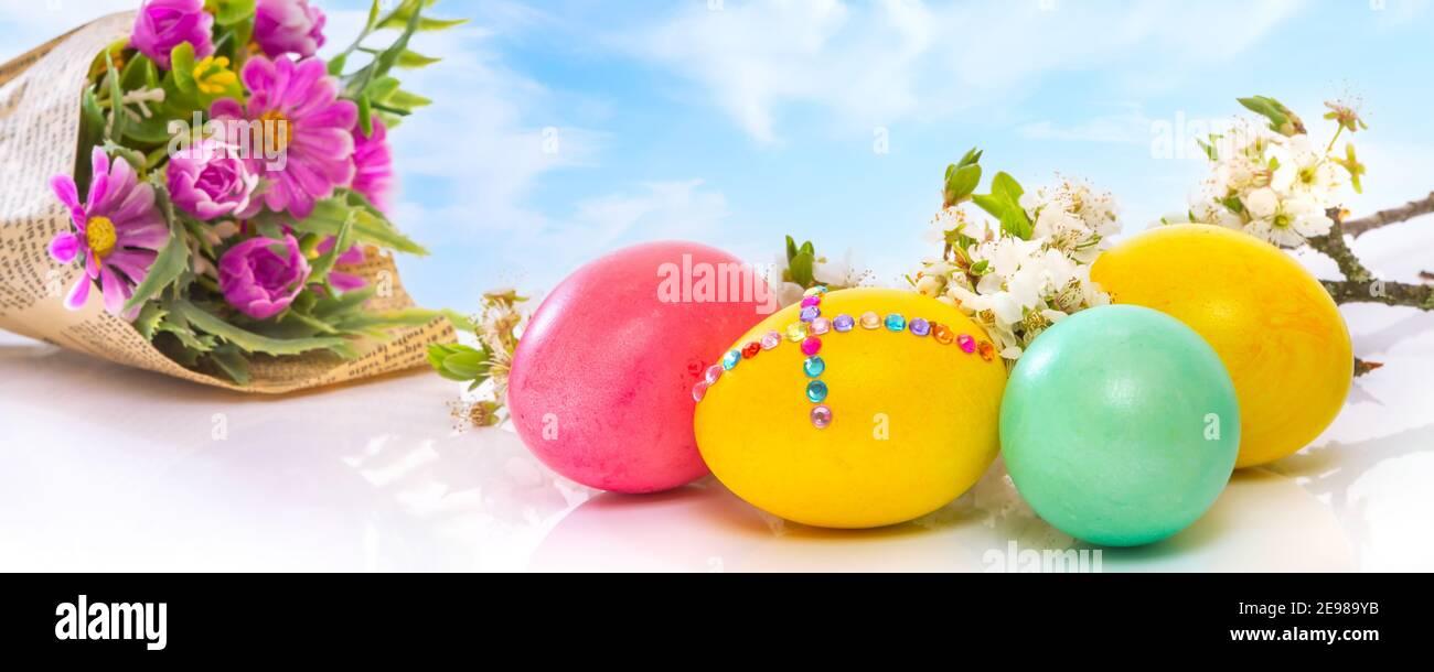 Huevos de Pascua de colores sobre el cielo azul nublado con ramo de flores, primer plano, banner de vacaciones Foto de stock