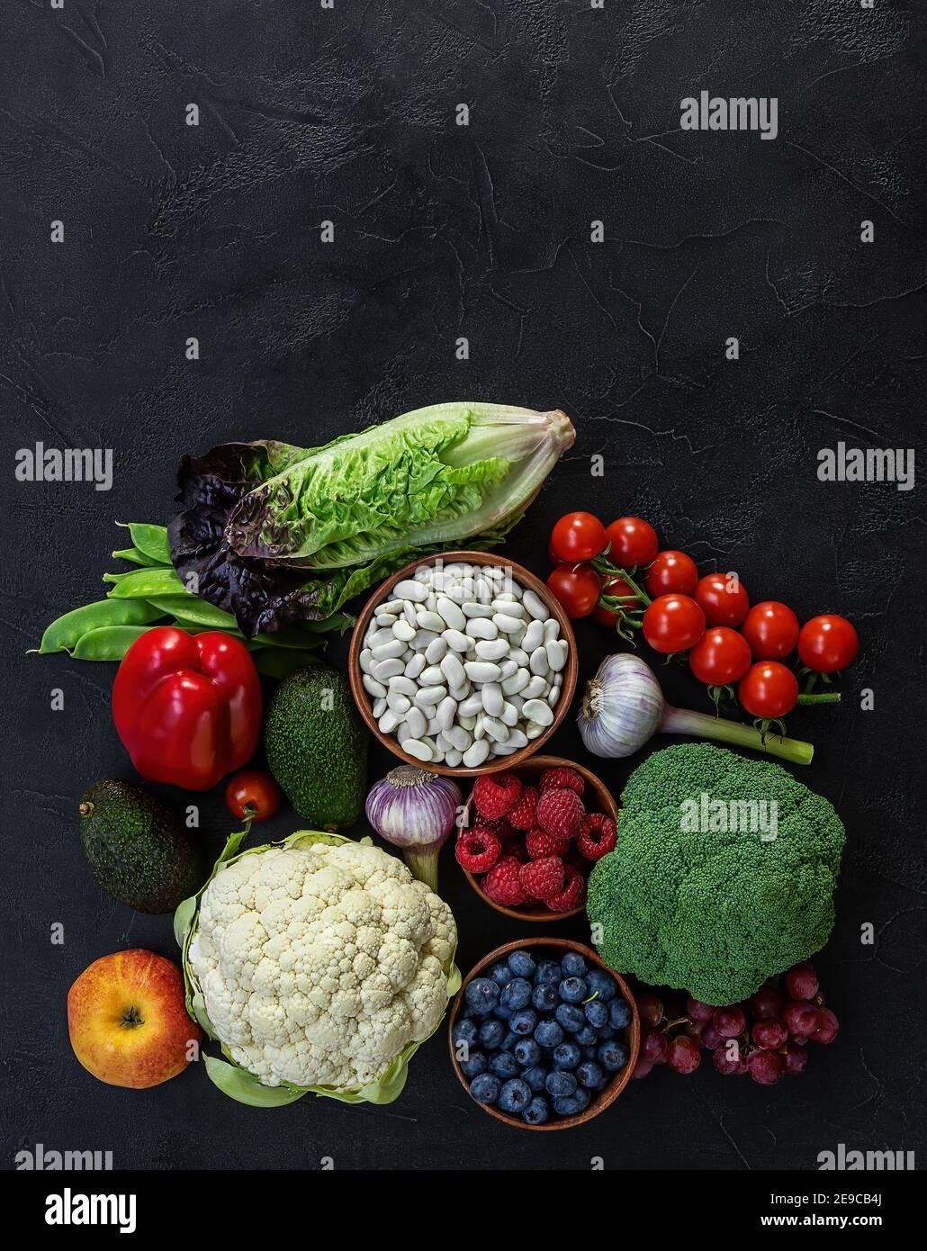 Fondo de alimentos saludables, productos de dieta a base de plantas de moda - verduras frescas crudas, bayas, y frijoles. Foto de stock