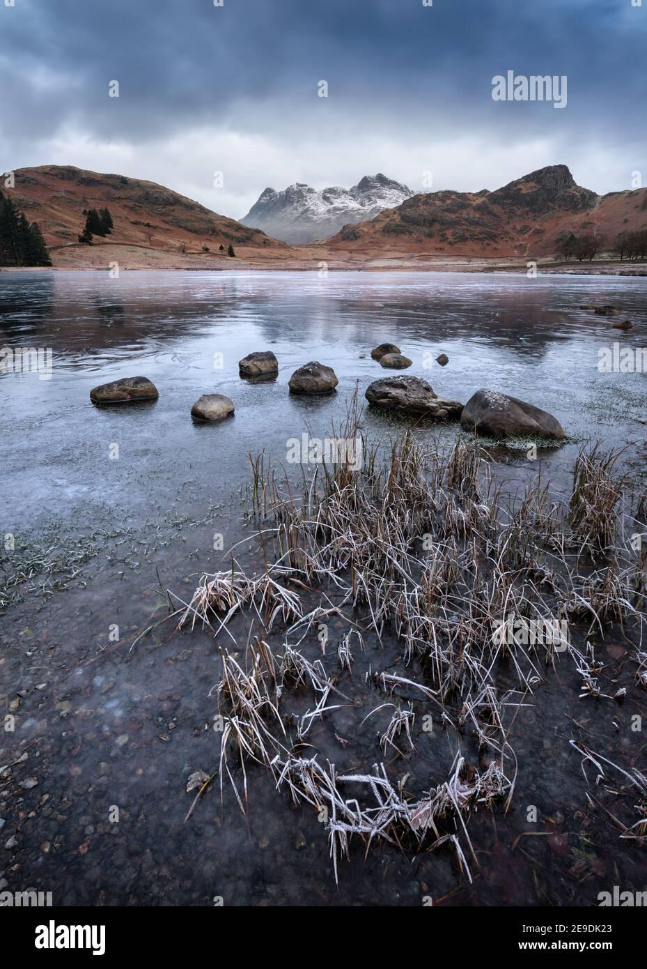 Lago congelado con hermosas vistas de las montañas nevadas en una mañana de invierno. Blea Tarn, Distrito de los Lagos, Reino Unido. Foto de stock