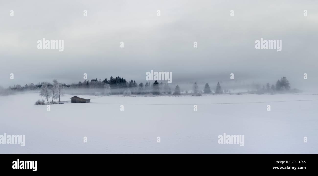 Panorama de hermoso paisaje invernal con árboles congelados y.. casa de madera Foto de stock