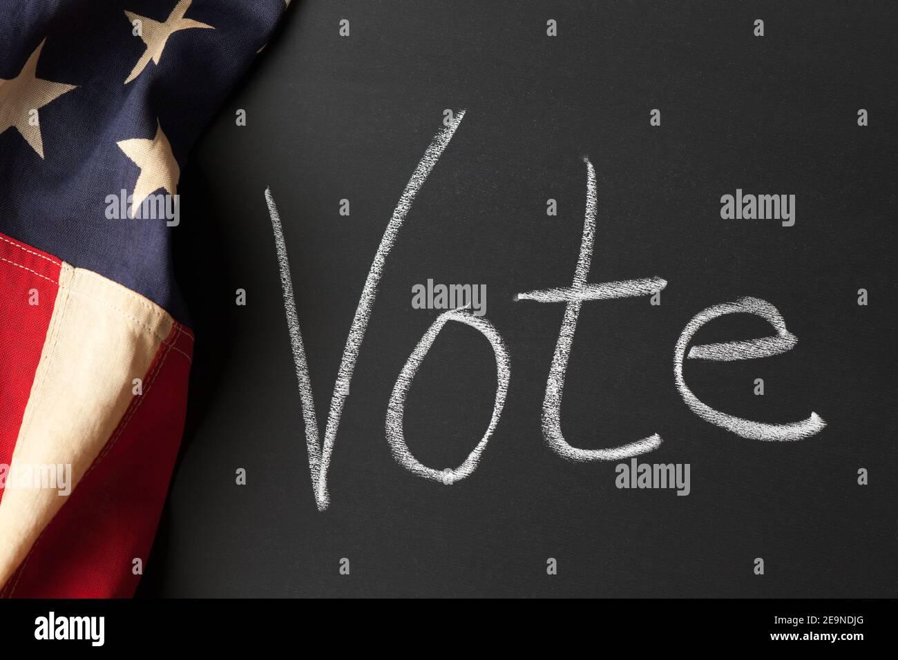 Un signo de voto escrito en una pizarra con la cosecha americana bandera Foto de stock