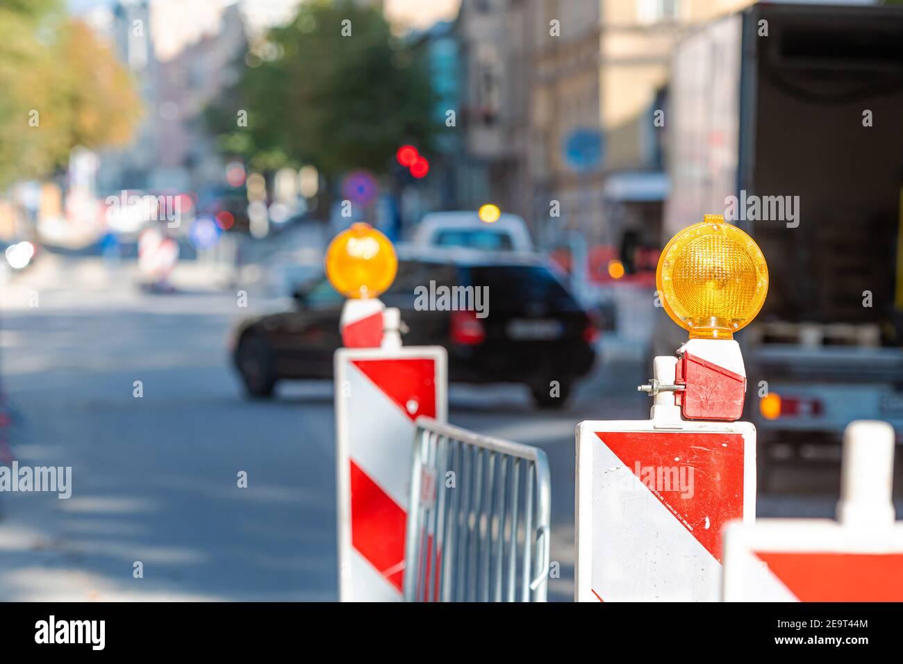 postes de advertencia con señal de luz naranja en la carretera sobre trabajos de reparación, calle borrosa con los coches sobre el fondo Foto de stock