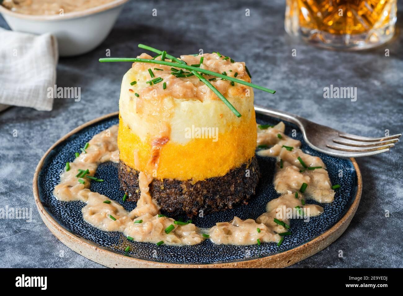 Haggis, neeps y tatties pila (haggis con nabos y patatas) con salsa de whisky - plato escocés tradicional para la noche de los burns Foto de stock