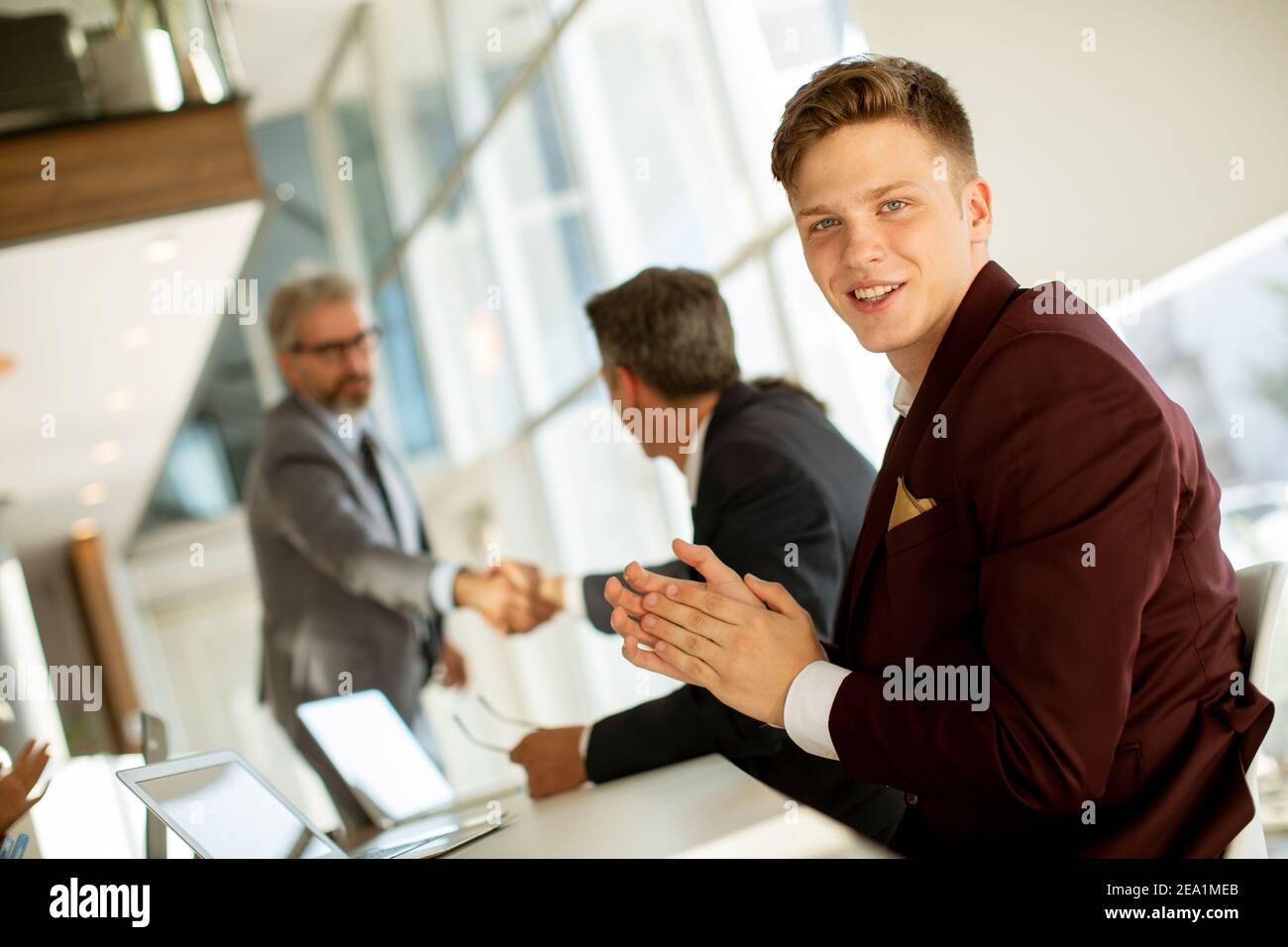 Un hombre joven y guapo golpeando las manos después de una exitosa reunión de negocios la oficina moderna Foto de stock