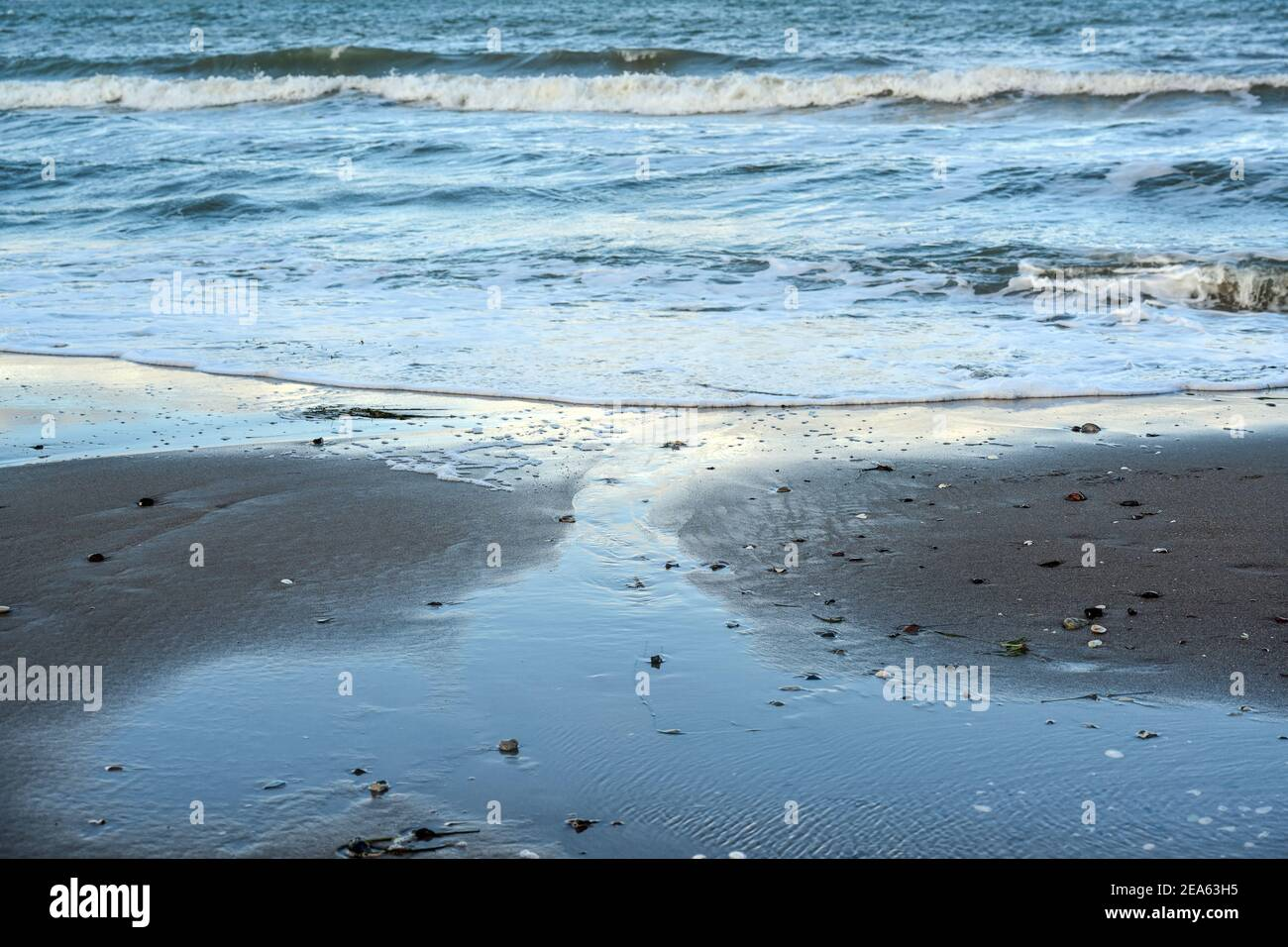 Playa de mar con olas azules y aguas poco profundas en la arena mojada, fondo marino para vacaciones y viajes temas, copiar espacio, enfoque seleccionado, estrecho de Foto de stock