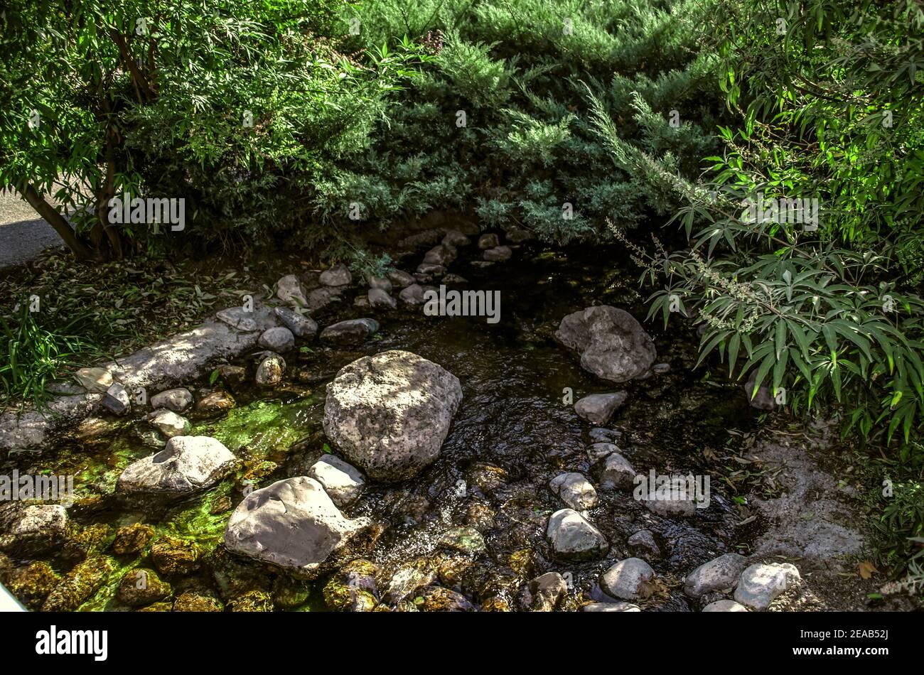 Un arroyo artificial que fluye a través de todo el parque con rápidos rocosos y plantas ornamentales creciendo a lo largo de las orillas Foto de stock