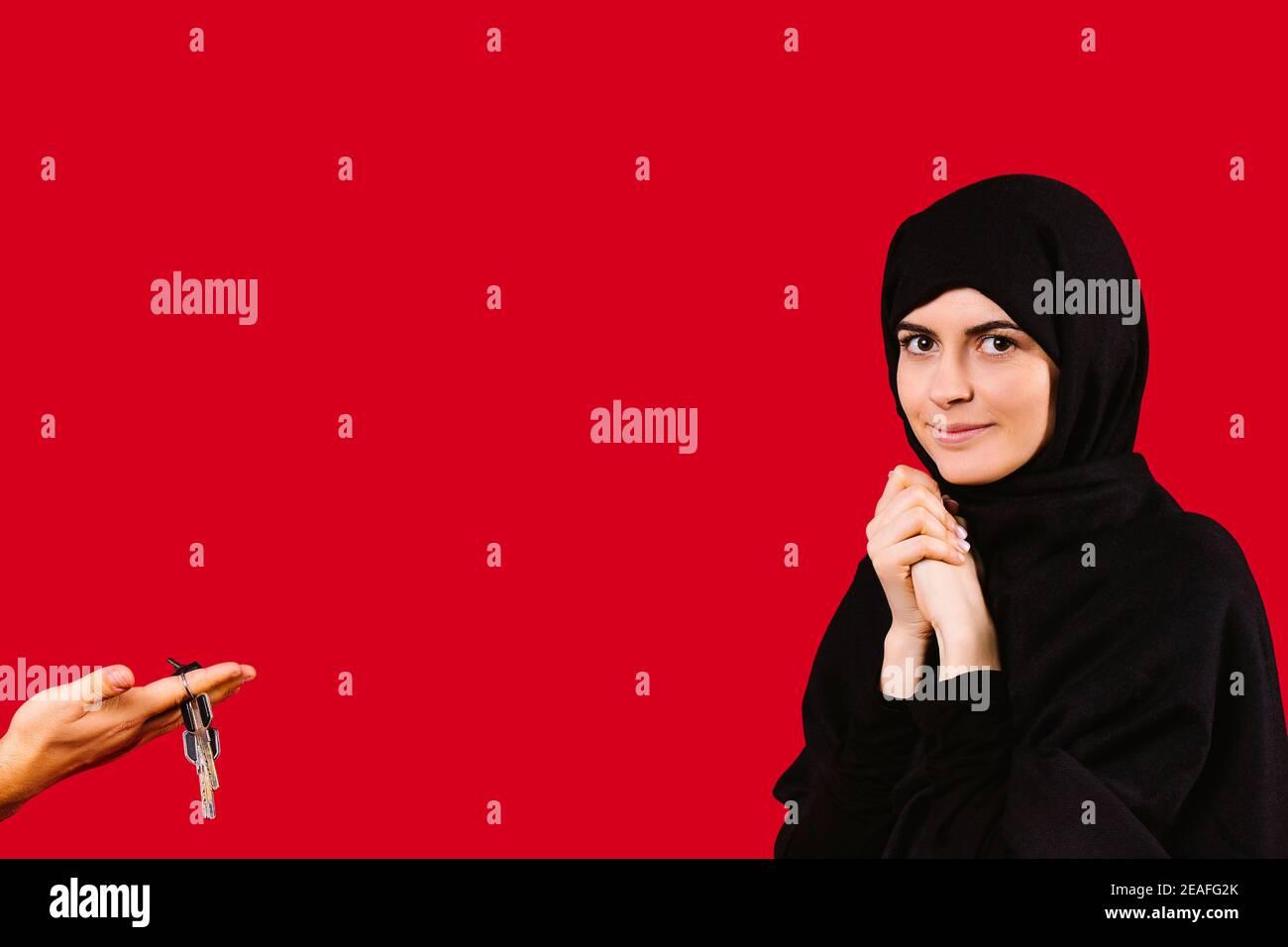 Chica joven sorprendida en negro hijab mira la cámara. La mano de un hombre sostiene las llaves del apartamento. Regalo para mujeres musulmanas sobre fondo rojo. Foto de stock