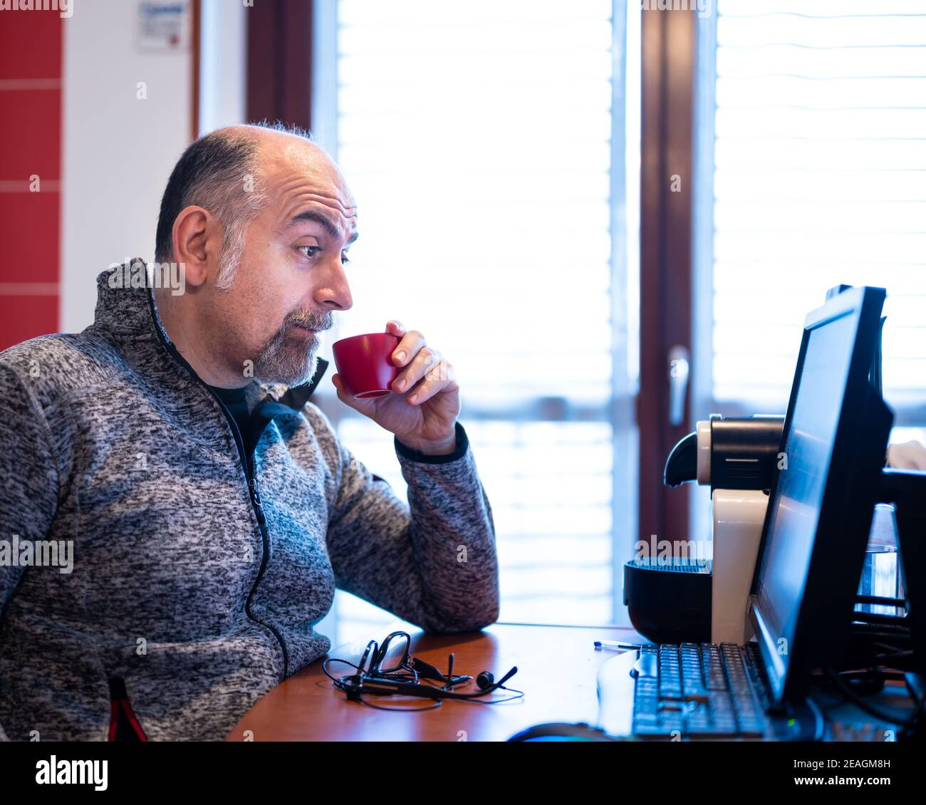 Un hombre caucásico de mediana edad que trabaja desde casa, mientras bebe un café, está agradablemente sorprendido por una notificación que lee en el monitor de su computadora. Foto de stock