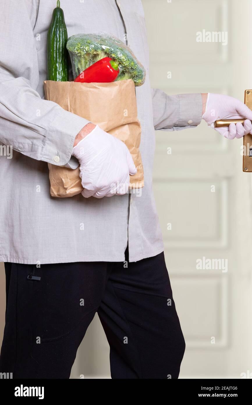 Un hombre que lleva guantes médicos y una bolsa de compras con verduras frescas entra en la casa. Concepto de fortalecimiento del sistema inmunitario y protección contra las infecciones por coronavirus. Foto de stock