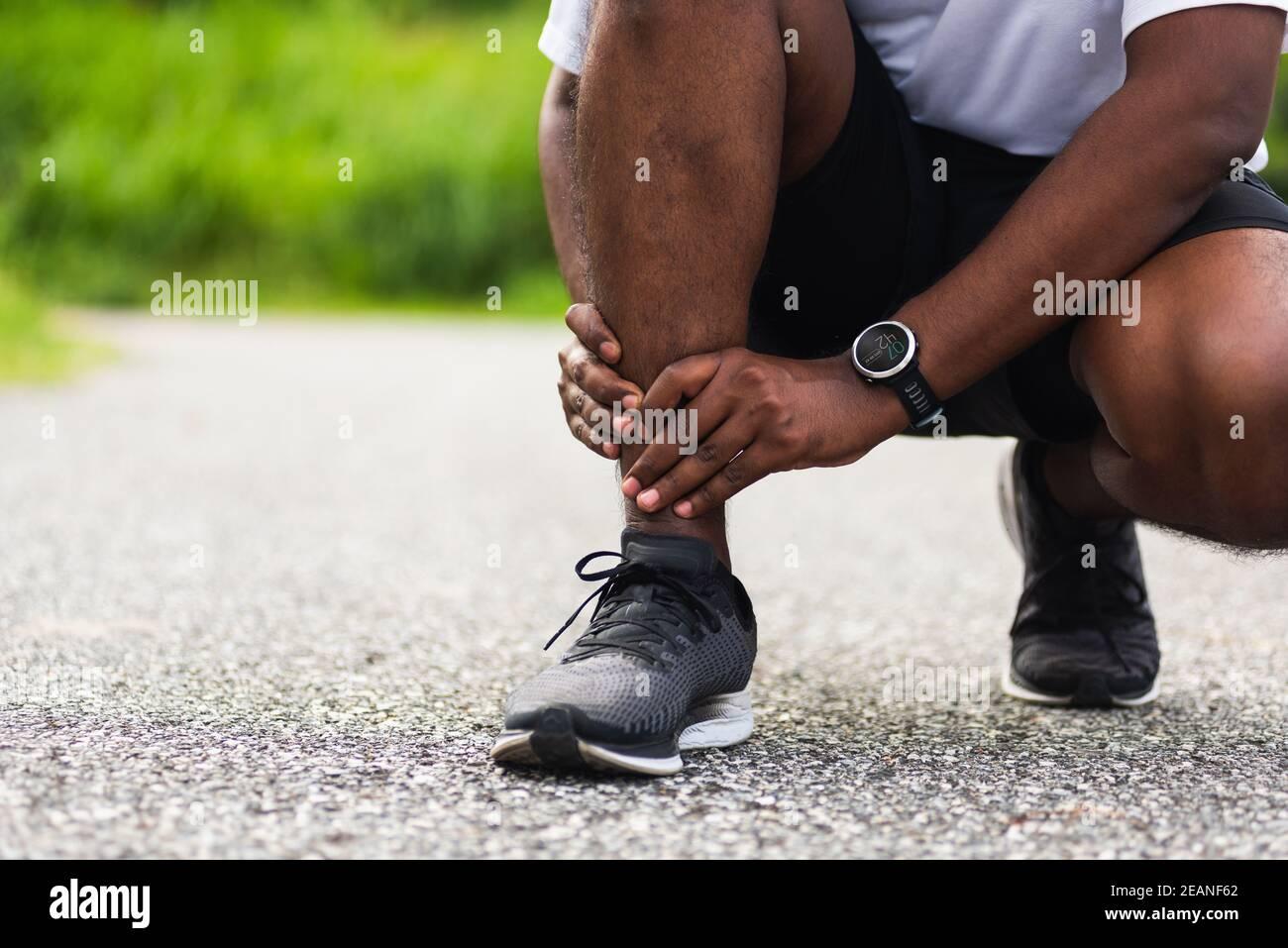 el hombre corredor de deporte usa las manos articulación sostener el dolor de la pierna porque de tobillo torcido roto mientras corres Foto de stock