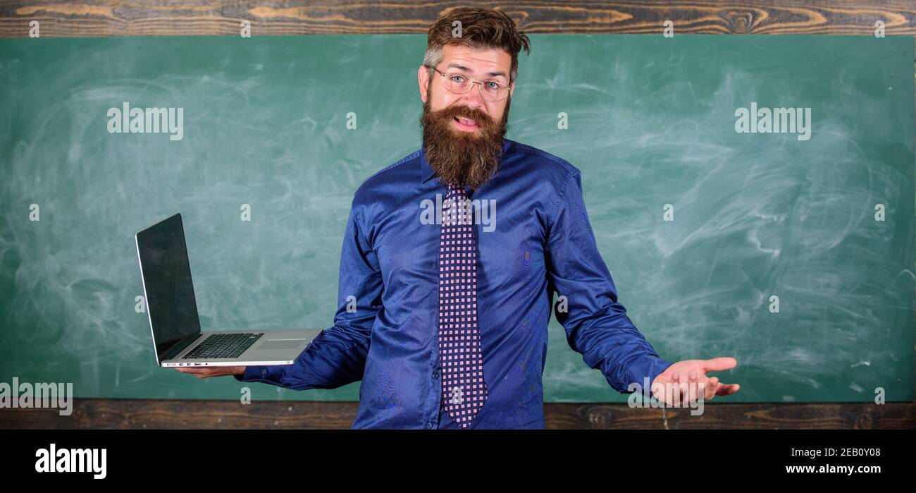 La enseñanza de las cuestiones utilizando las más modernas tecnologías. Profesor Hipster expresión confusa tiene portátil. Maestro hombre barbado confundirse trabajo portátil moderno con pizarra de fondo. Temas de educación a distancia. Foto de stock