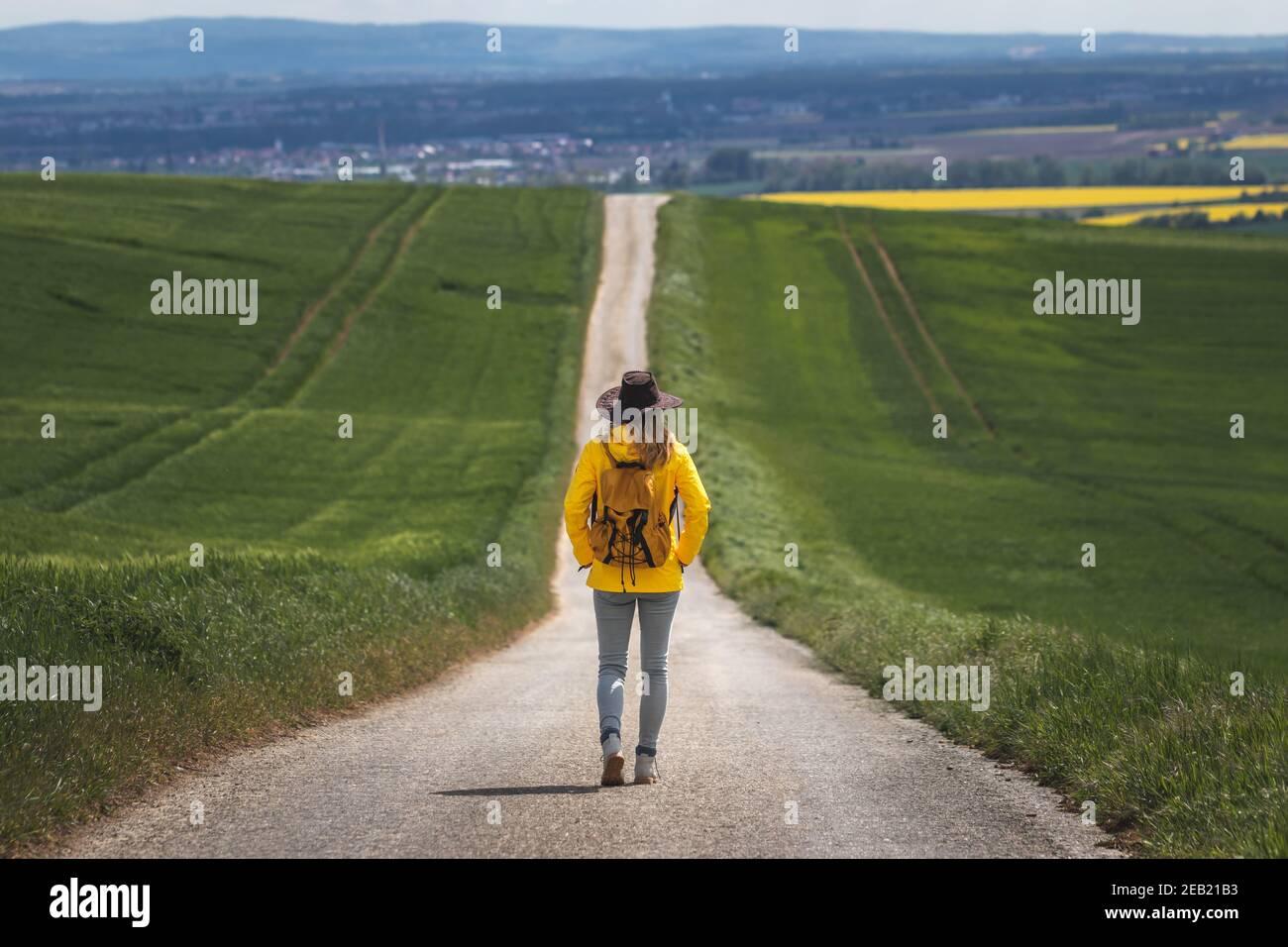 Largo viaje. Mujer de senderismo caminando en camino vacío. Hiker con sombrero y mochila con chaqueta impermeable amarilla. Concepto de viaje. Alejándose de ella Foto de stock