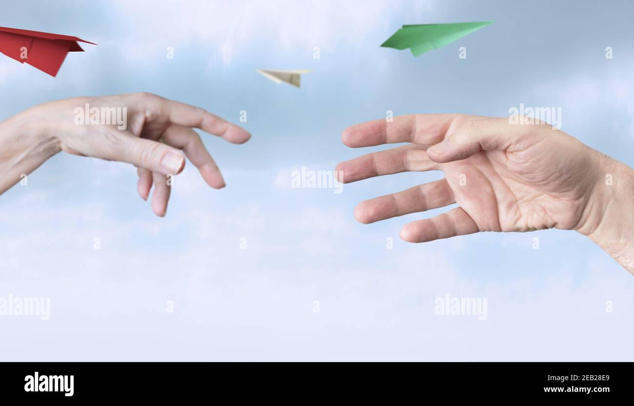 Dos manos (hombre, mujer) lanzan aviones de papel multicolores, fondo del cielo. Foto de stock