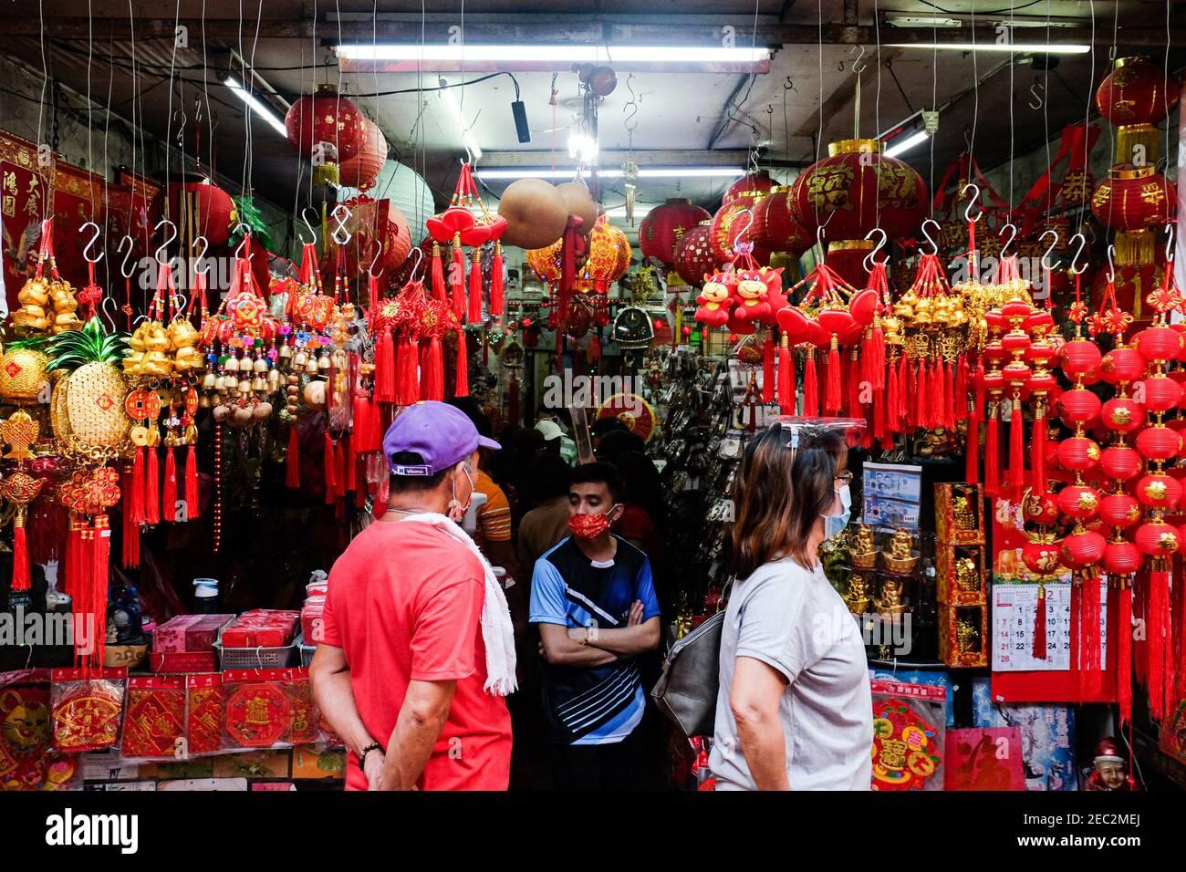 Ongpin St., Binondo, Manila, Filipinas. 13 de febrero de 2021. La gente que busca encantos afortunados para comprar en Ongpin St., Binondo, durante el año Nuevo Chino. Binondo es conocido como el barrio chino más antiguo del mundo, la mayoría de las celebraciones como bailes de dragón y león fueron canceladas debido a la pandemia. Crédito: Mayoría Mundial CIC/Alamy Live News Foto de stock