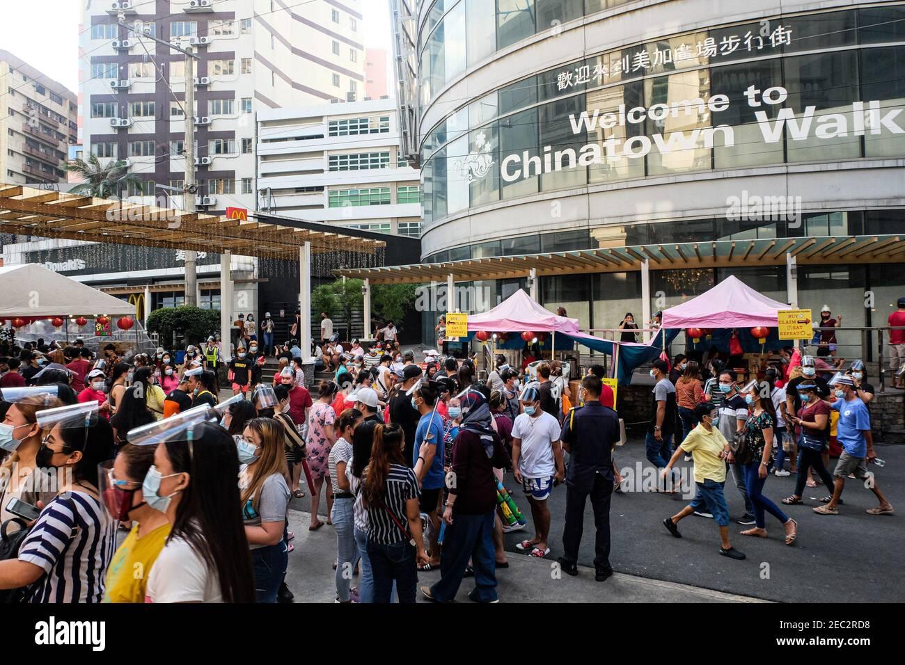 Ongpin St., Binondo, Manila, Filipinas. 13 de febrero de 2021. La gente que lleva máscaras y escudos de la cara camina por las calles adornadas con faroles chinos en Ongpin, Binondo durante la celebración del año Nuevo Chino. Binondo es conocido como el barrio chino más antiguo del mundo, la mayoría de las celebraciones como bailes de dragón y león fueron canceladas debido a la pandemia. Crédito: Mayoría Mundial CIC/Alamy Live News Foto de stock