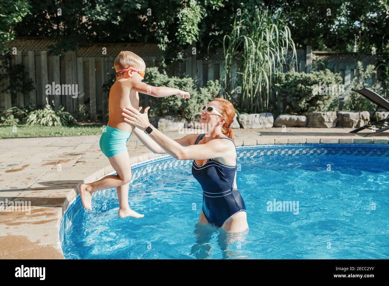 Madre caucásica entrenando a su hijo pequeño para nadar en la piscina al aire libre. Niño zambulléndose en el agua con gafas. Actividad estacional de la familia del agua Foto de stock