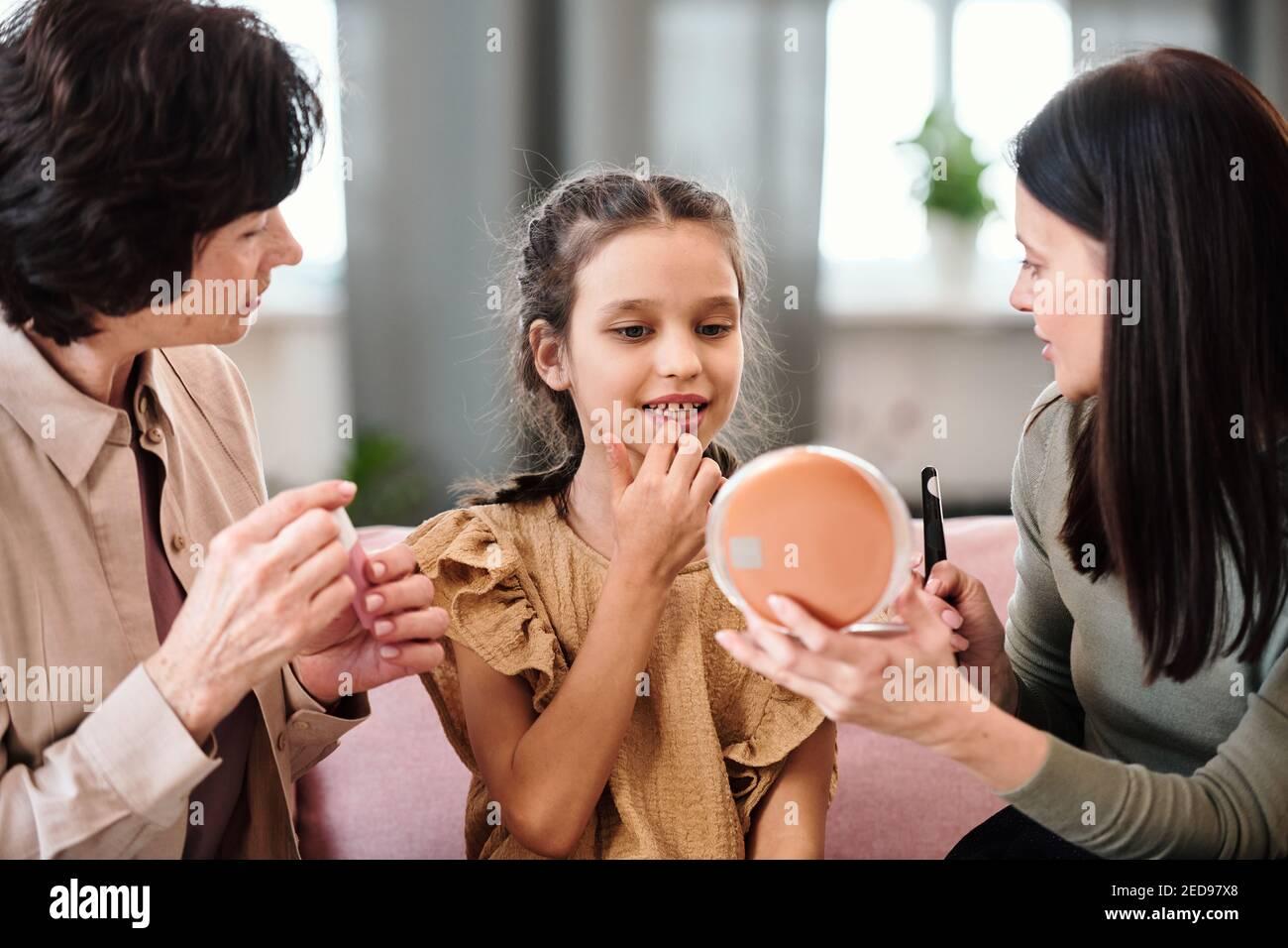 Linda niña en vestido aplicando bálsamo nutritivo en los labios mientras que mira en el espejo sostenido por la joven morena mujer dando su consejo de belleza Foto de stock