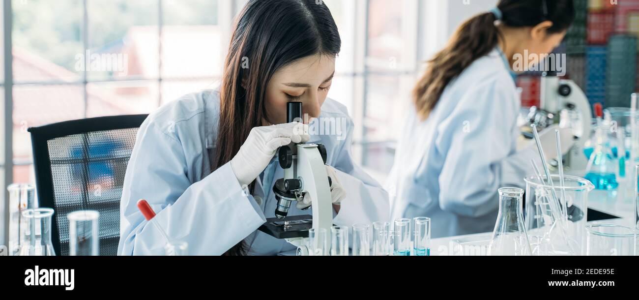 Joven científica asiática que hace investigación en laboratorio que usa laboratorio abrigo y guantes con colega en el fondo para desarrollar antivirus vacuna Foto de stock