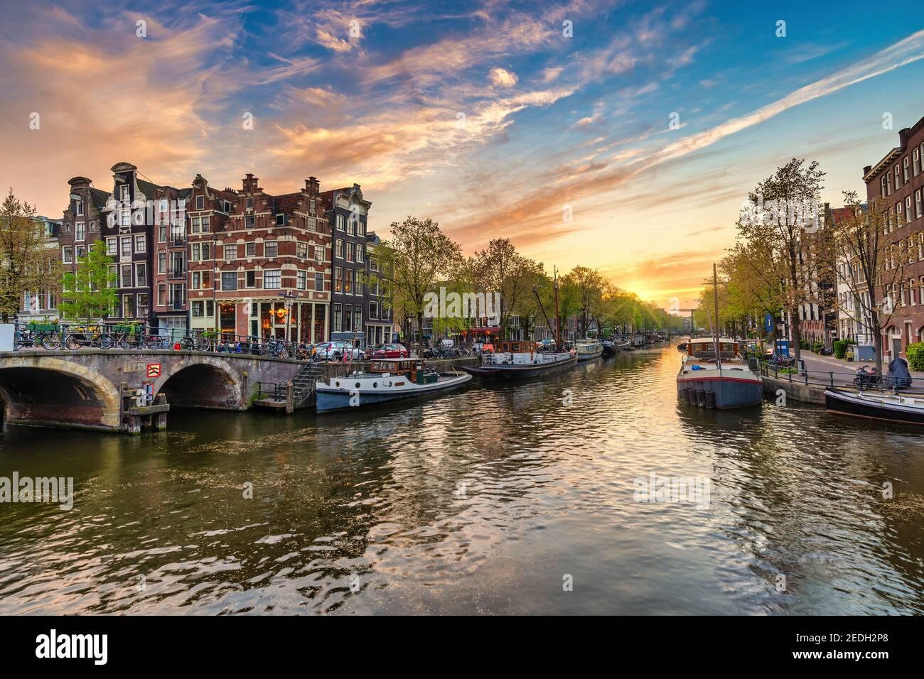 Amsterdam, Países Bajos, atardecer, el horizonte de la ciudad de casa holandesa en canal waterfront Foto de stock