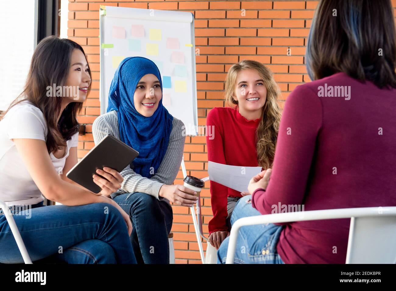 Grupo de mujeres diversas con ropa casual y colorida sentada reunión circular para el proyecto social Foto de stock