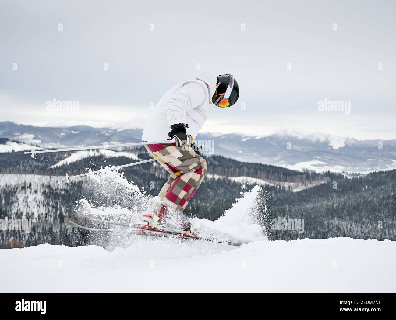 Toda la longitud de esquí alpino esquiador en nieve fresca en polvo en las montañas de invierno. Hombre freerider en invierno pantalones de esquí haciendo saltar mientras se desliza por las pistas cubiertas de nieve. Concepto de deportes de invierno. Foto de stock