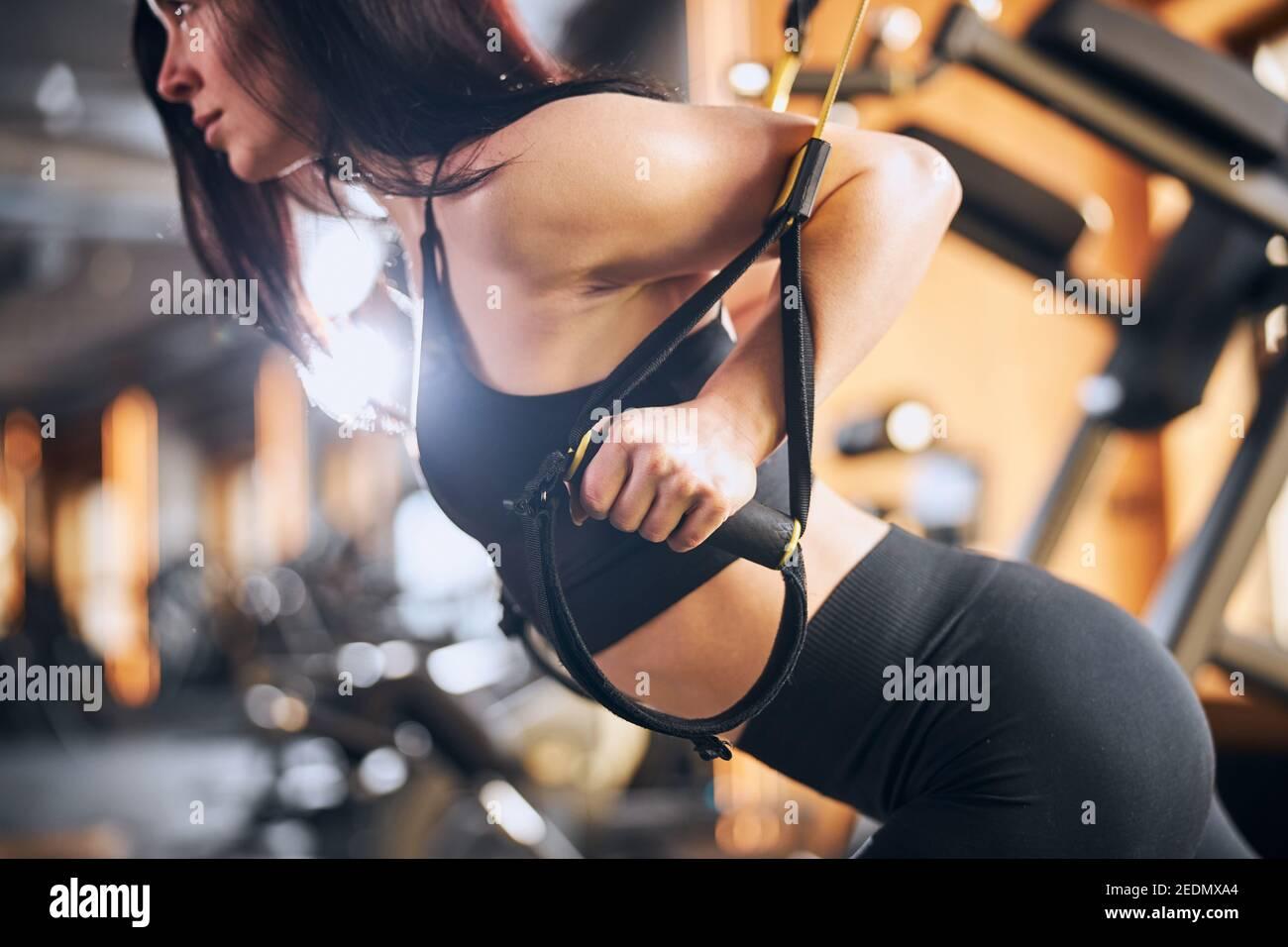 Mujer joven atlética haciendo ejercicio con correas de fitness Foto de stock