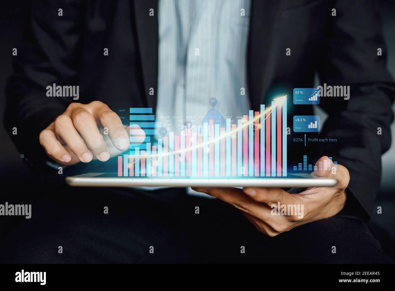 Empresario inversor analizando informe de fondo mutuo financiero de la empresa trabajando con la tecnología digital de gráficos de realidad aumentada. Foto de stock