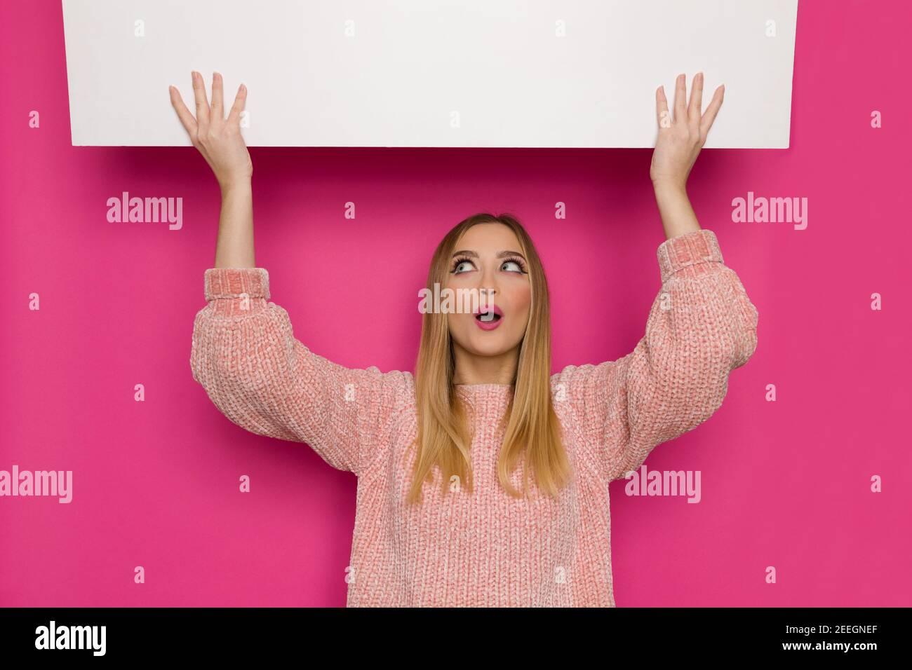 Mujer joven sorprendida en suéter rosa está sosteniendo una pancarta blanca sobre la cabeza, mirando y hablando. Vista frontal. Estudio de cintura arriba sobre fondo rosa. Foto de stock