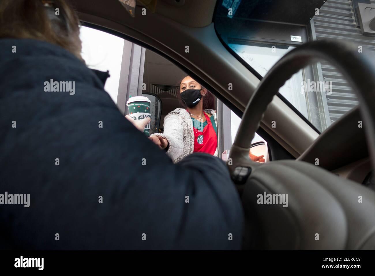 Patrón recibiendo café del servidor en Starbucks Drive-Thru ventana usando máscaras durante Covid Pandemic. St Paul Minnesota MN EE.UU Foto de stock