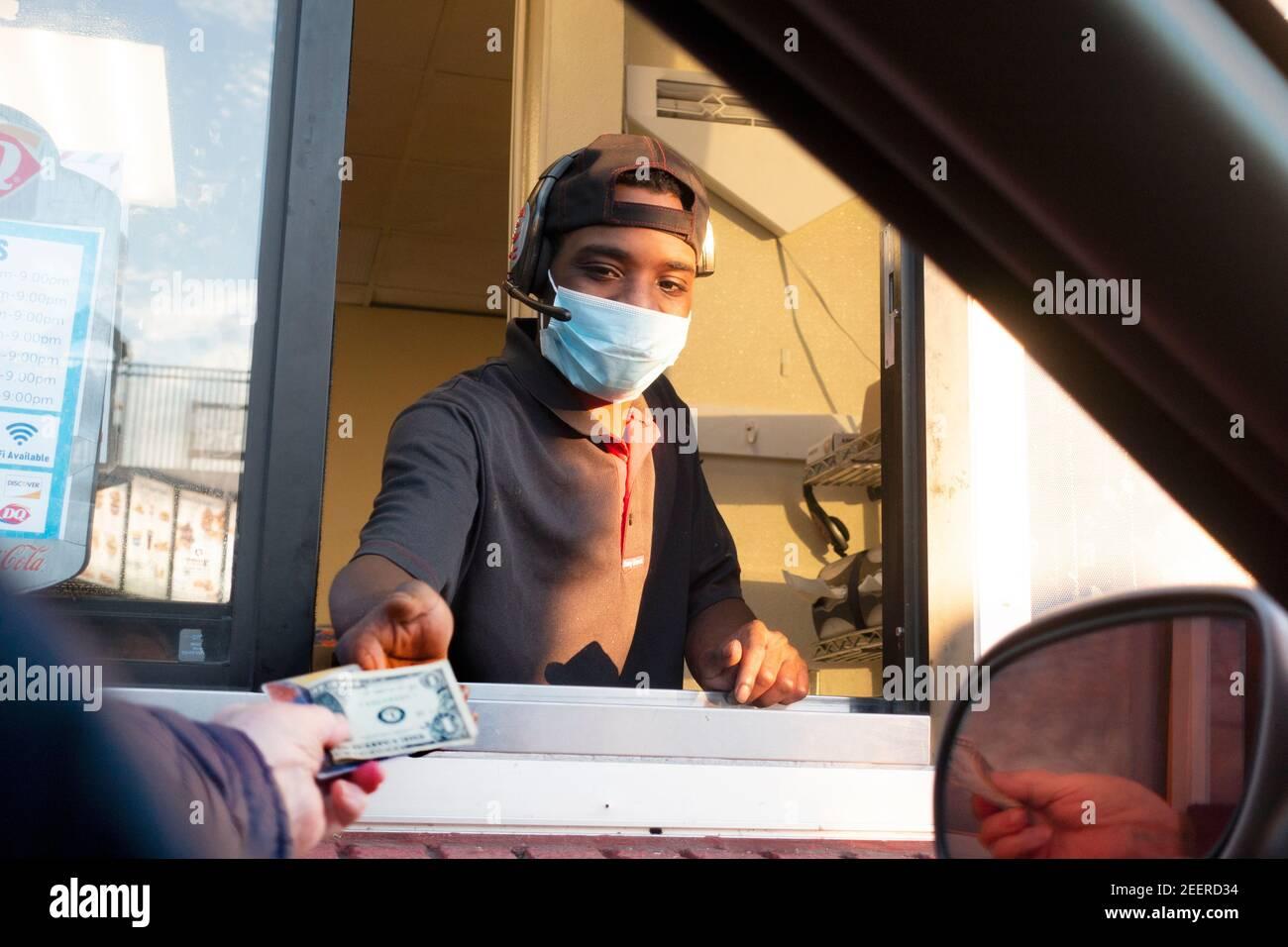 Cliente entregando a trabajador enmascarado una propina y una tarjeta para pagar por una Dairy Queen en la ventana de la unidad. St Paul, Minnesota Minnesota, Minnesota, EE.UU Foto de stock