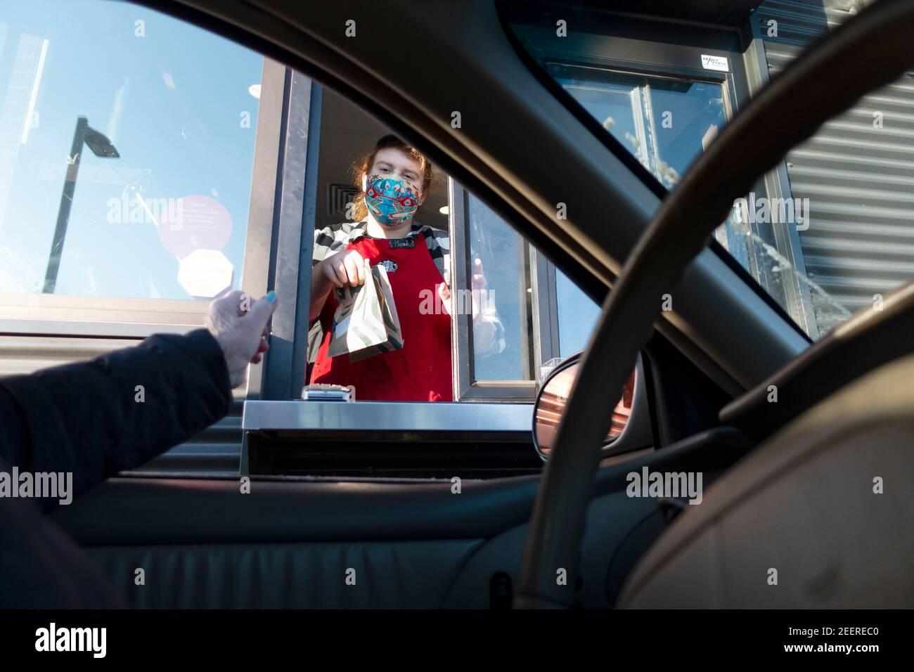 Cajero de Starbucks enmascarado entregando la bolsa de la patrona de los pasteles mientras que el café se está preparando durante la Pandemic de Covid. St Paul Minnesota MN EE.UU Foto de stock