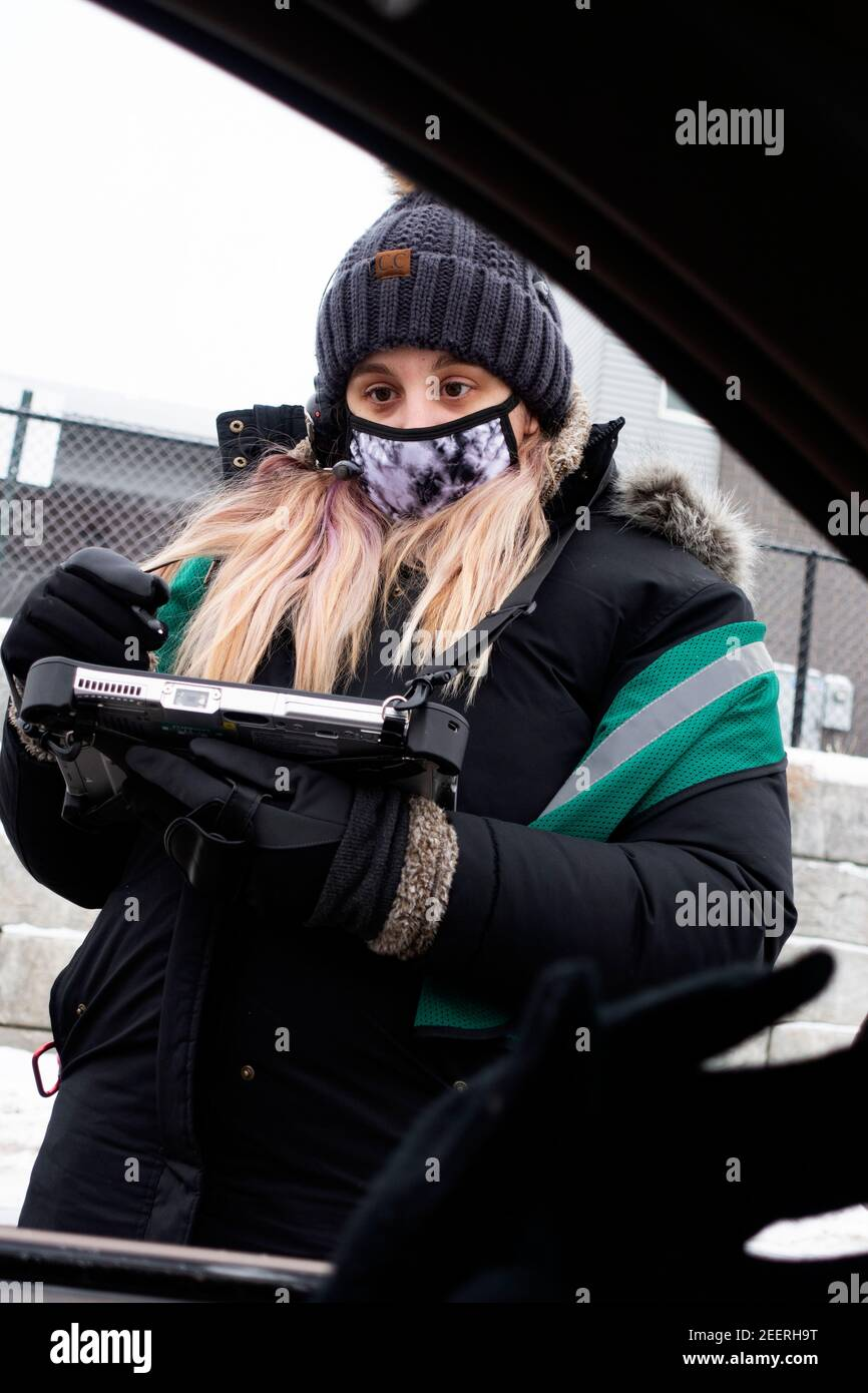 Mujer enmascarada tomando un pedido de café en Starbucks Drive-Thru durante Covid Pandemic en clima frío. St Paul Minnesota MN EE.UU Foto de stock