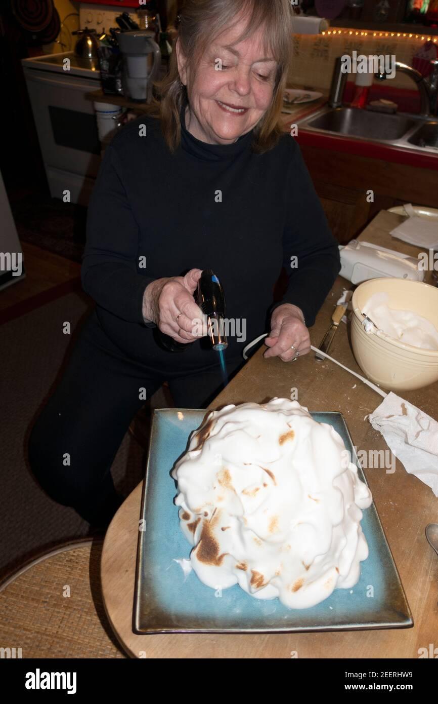 Mujer feliz usando una antorcha de cocina para pulir el merengue en una Alaska al horno. St Paul Minnesota MN EE.UU Foto de stock
