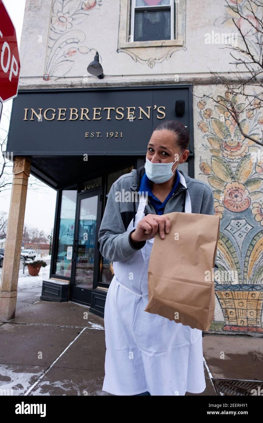 Carnicero de la tienda sueca de Ingebretsen que trae orden de lutefisk al lado del curbside. Minneapolis Minnesota MN EE.UU Foto de stock